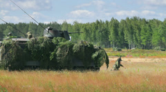Armoured fighting vehicle shoots in the field, soldiers take up position Stock Footage