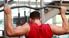 Fit man using the weights machine for his arms - stock footage