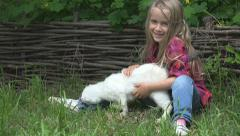 Little Girl Petting Cat on Grass in Yard, Countryside, Child Playing with Kitten Stock Footage