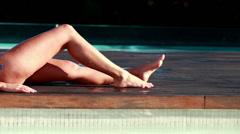 Sexy blonde in blue bikini relaxing lying poolside Stock Footage