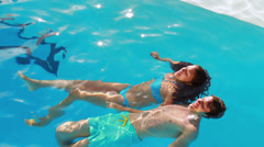 Couple floating in the swimming pool Stock Footage