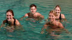 Four smiling people doing water aerobics in swimming pool Stock Footage