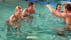 Fit people doing an aqua aerobics class in swimming pool - stock footage