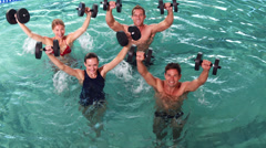 Fit people doing an aqua aerobics class in swimming pool with foam dumbbells - stock footage