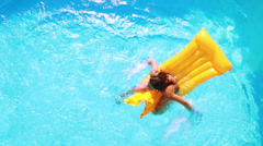 Overhead of brunette sitting on lilo in pool on sunny day Stock Footage