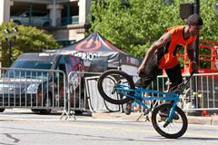 man practices flatland bmx tricks before competition - stock photo