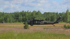 Military helicopter in the field near the forest, Black Hawk Stock Footage