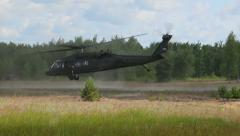 Military helicopter take off in the field near the forest, Black Hawk Stock Footage