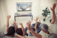 Family cheering and watching the world cup at home - stock photo