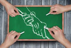 Stock Photo of Composite image of multiple hands drawing handshake with chalk