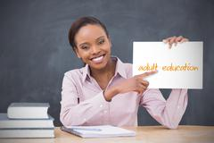 Stock Photo of Happy teacher holding page showing adult education