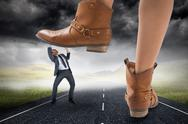 Stock Illustration of Composite image of cowboy boots stepping on businessman
