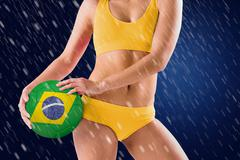 Stock Photo of Composite image of fit girl in yellow bikini holding brazil football