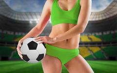 Composite image of fit girl in green bikini holding football Stock Photos