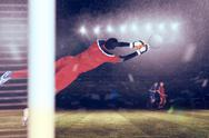 Stock Illustration of Composite image of goalkeeper in red making a save