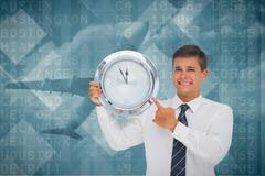 Composite image of anxious businessman holding and showing a clock Stock Illustration