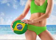 Composite image of fit girl in green bikini holding brasil ball - stock photo