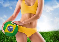 Composite image of fit girl in yellow bikini holding brazil football - stock photo