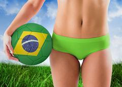 Stock Photo of Composite image of fit girl in green bikini holding brazil football