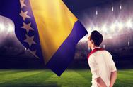 Stock Illustration of Composite image of handsome football fan looking ahead