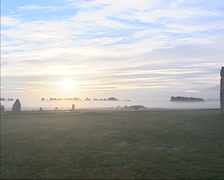 Stonehenge at daybreak in mist + pan - wide shot stone circle Stock Footage