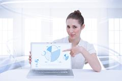 Composite image of businesswoman showing a laptop - stock photo