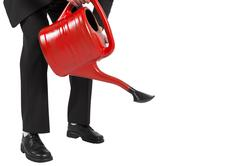 Businessman watering with red can Stock Photos
