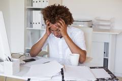 Casual stressed businessman with his head down at desk - stock photo