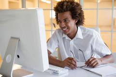 Stock Photo of Casual young businessman sitting at his desk smiling at computer