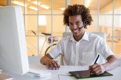 Casual young businessman using digitizer and headset at desk - stock photo