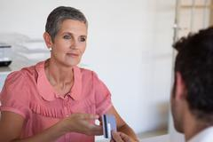 Casual saleswoman taking credit card from customer - stock photo
