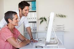Stock Photo of Casual business team working together at desk using computer