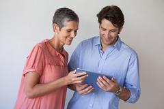 Casual smiling business team looking at tablet pc together - stock photo