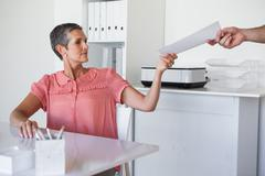 Stock Photo of Casual businesswoman handing document to colleague