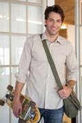 Casual businessman standing with his skateboard smiling at camera - stock photo