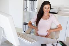 Stock Photo of Casual pregnant businesswoman touching her bump at her desk smiling at camera