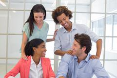 Coworkers congratulating and praising each other - stock photo