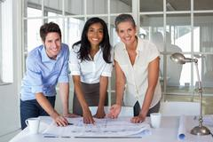 Stock Photo of Architects working on blueprints smile to camera