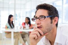 Casual businessman with glasses concentrating - stock photo