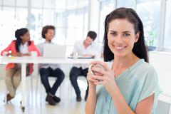 Stock Photo of Attractive businesswoman drinking hot beverage with colleagues in background