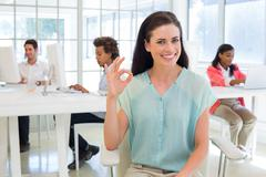 Attractive businesswoman giving OK sign to camera - stock photo