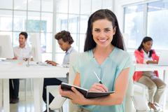 Attractive businesswomen writing in notebook with colleagues behind her - stock photo