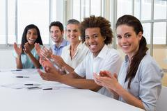 Business people clapping and smiling at camera Stock Photos