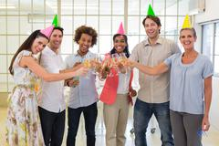 Colleagues celebrate success by having a party and smile at camera Stock Photos