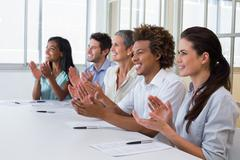 Casual business team clapping at presentation - stock photo
