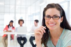 Stock Photo of Attractive businesswoman smiling at camera with coworkers in background