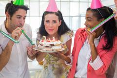 Businesswoman blowing out candles on cake Stock Photos