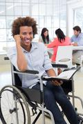 Businessman in wheelchair holding planner and smiling at camera Stock Photos