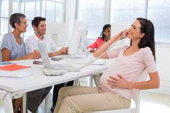 Businesswoman on the phone and strokes preganat belly - stock photo