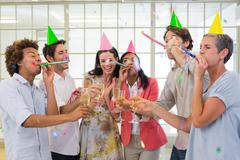 Stock Photo of Casual business team celebrating with champagne and party horns